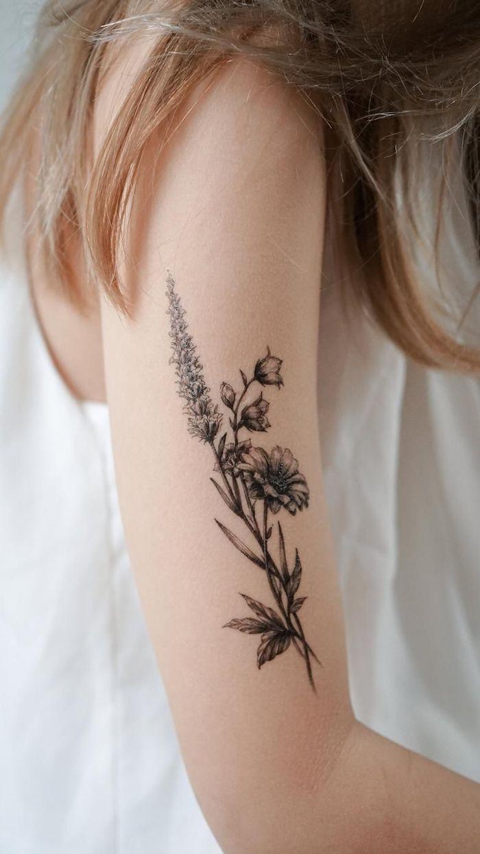 tatouage floral delicate sur le bras d une femme vetue en blanc