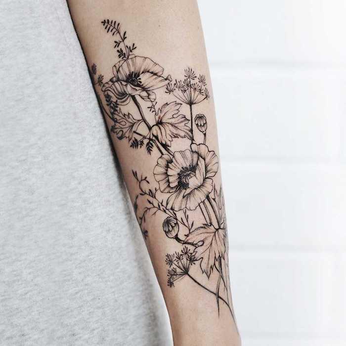 tatouage ornemental avec des fleurs en noir et blanc sur l avant bras