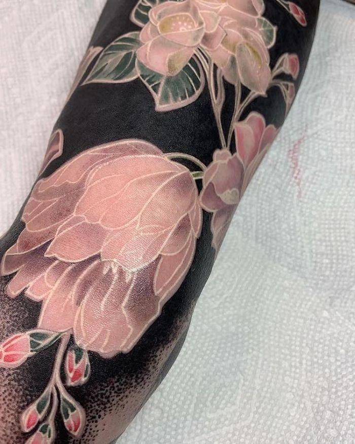 tatouage style renaissance avec des fleurs en couleur nu sur un fond noir