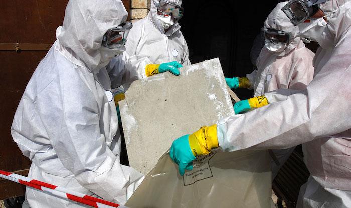 traitement de l amiante execute par des specialistes en costumes blancs