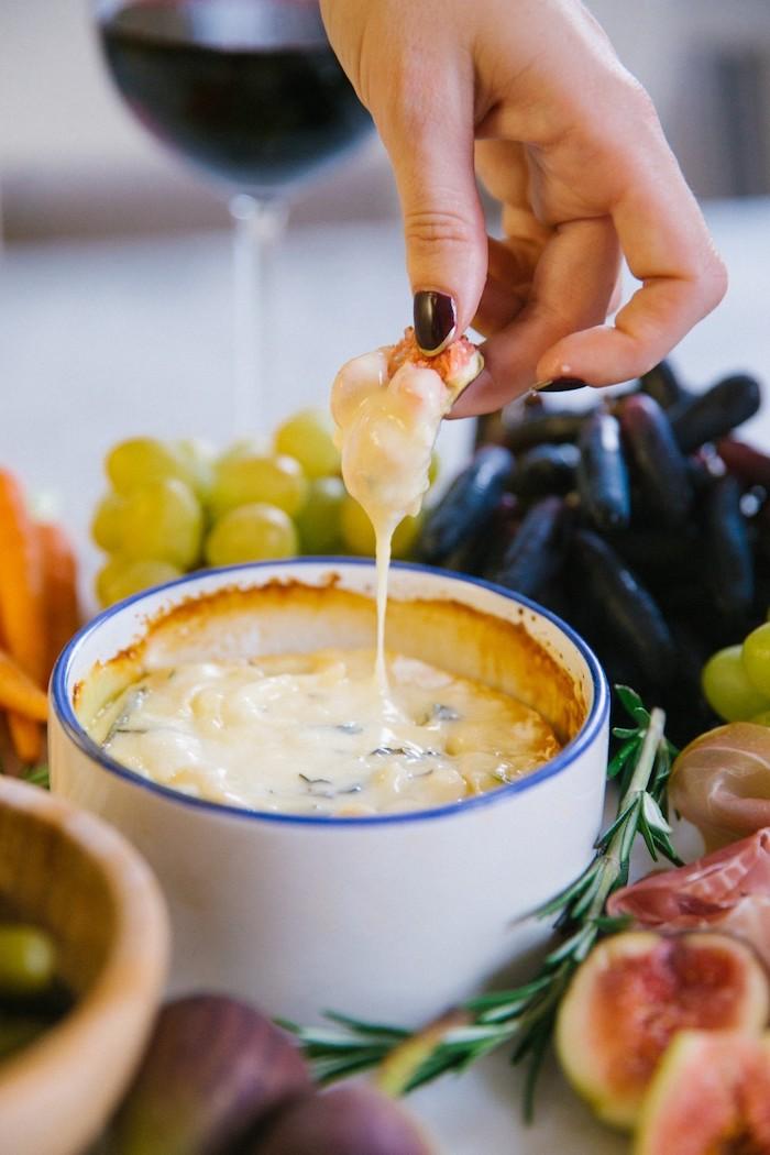 un camembert chaud dans un bol pour manger avec des fruits et d une verre de vin rouge