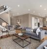 un canapé gris et deux fauteils beiges dans un apartement avec escalier