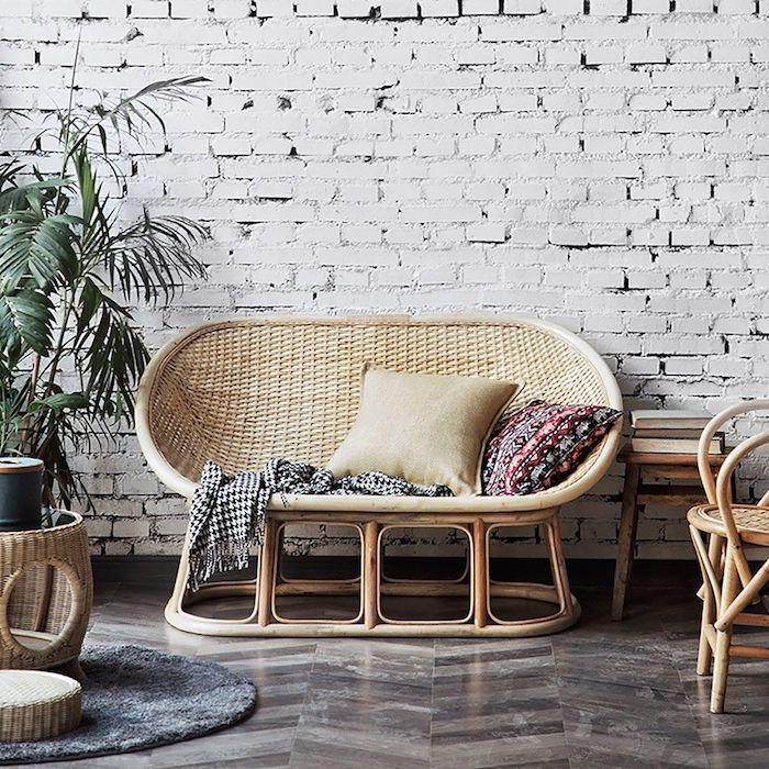 un canape en forme ovale et en osier devant un mur en briques pres d une table basse en rotin
