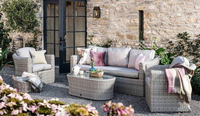 un ensemble des meubles en rotin devant une grande maison en pierre avec des coussins et des fleurs roses