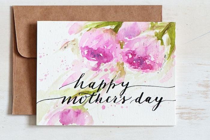 un envelopp dessous une carte peint a l aquarelle avec des fleurs et un message caligraphe