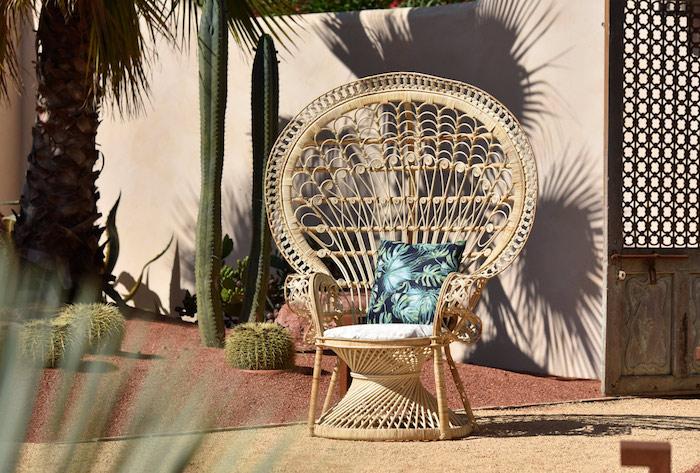 un fautueil en rotin en forme extravagante dans le jardin avec des cactus