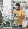 un homme avec barbe qui peint un fauteuil en rotin avec des pinceaux