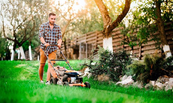 un homme équipée d une tondeuse tond la pelouse dans le jardin