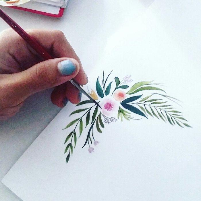 un main ongles bleu dessin avec un piceau fin des elements floraux