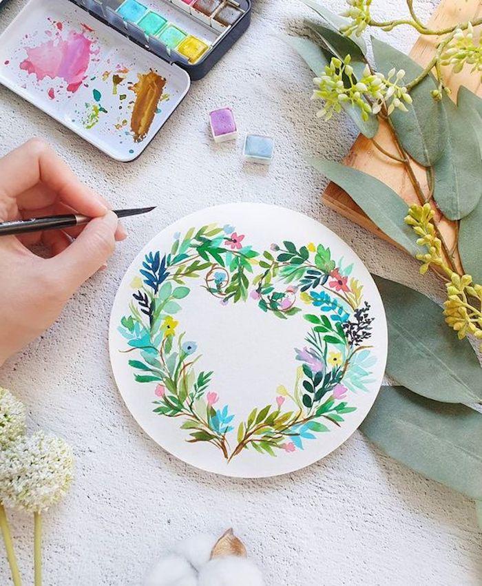 un main qui fait essin aquarelle avec flurs sur un papier forme cercle a coté des branches