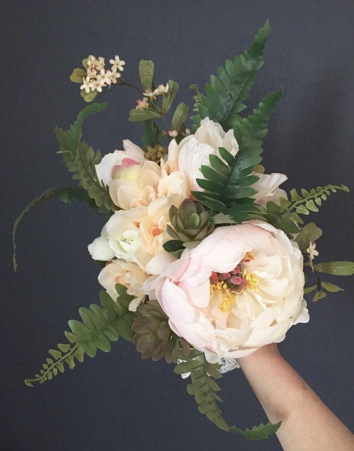 un main qui tinent un bouquet des pivoines roses et des paprates vertes