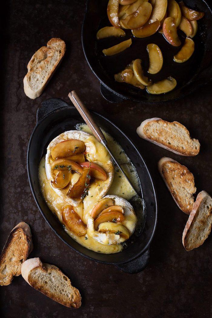 un plat de camember roti au meil avec des tranches de pomme et des croustini dans petites poeles noires