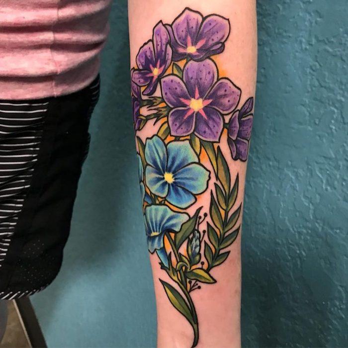 un tatouage bras femme fleur au fond bleu avec des fleurs en style new school