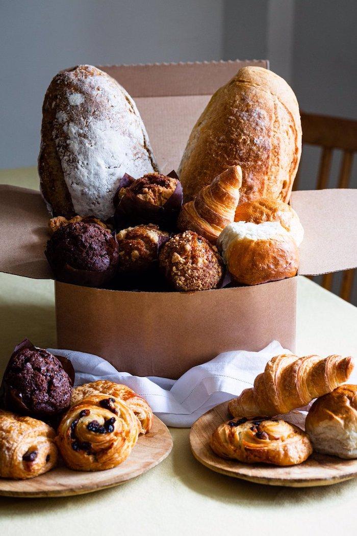 une biote remplie des produits de pain et des patisseries dans deux assiettes en bois