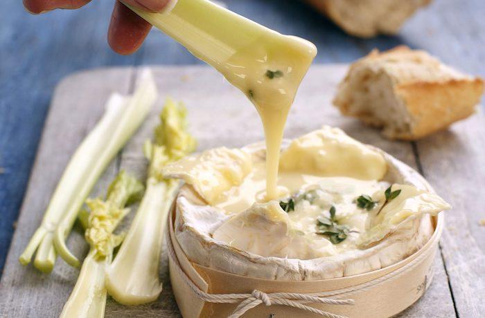 une boite de camembert roti et fondue et un main qui trempe une tige de céléry