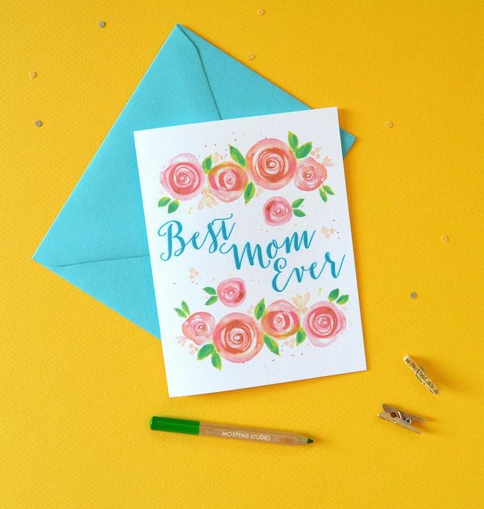 une carte avec fleurs fete des meres avec un enveloppe bleu et un crayuon sur surface jaune