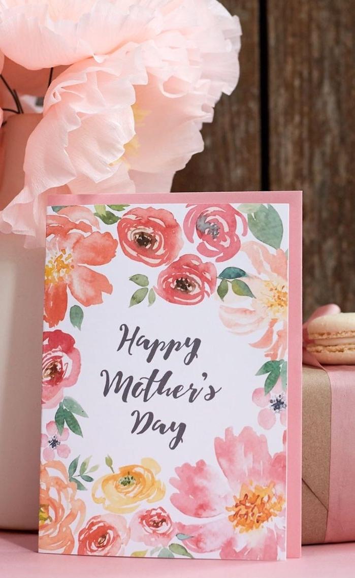 une carte en nuances roses a coté des fleurs artificiels et un macaron