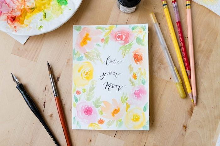 une carte peinte en aquarelle pour la fête des mères avec des pinceaux et crayons