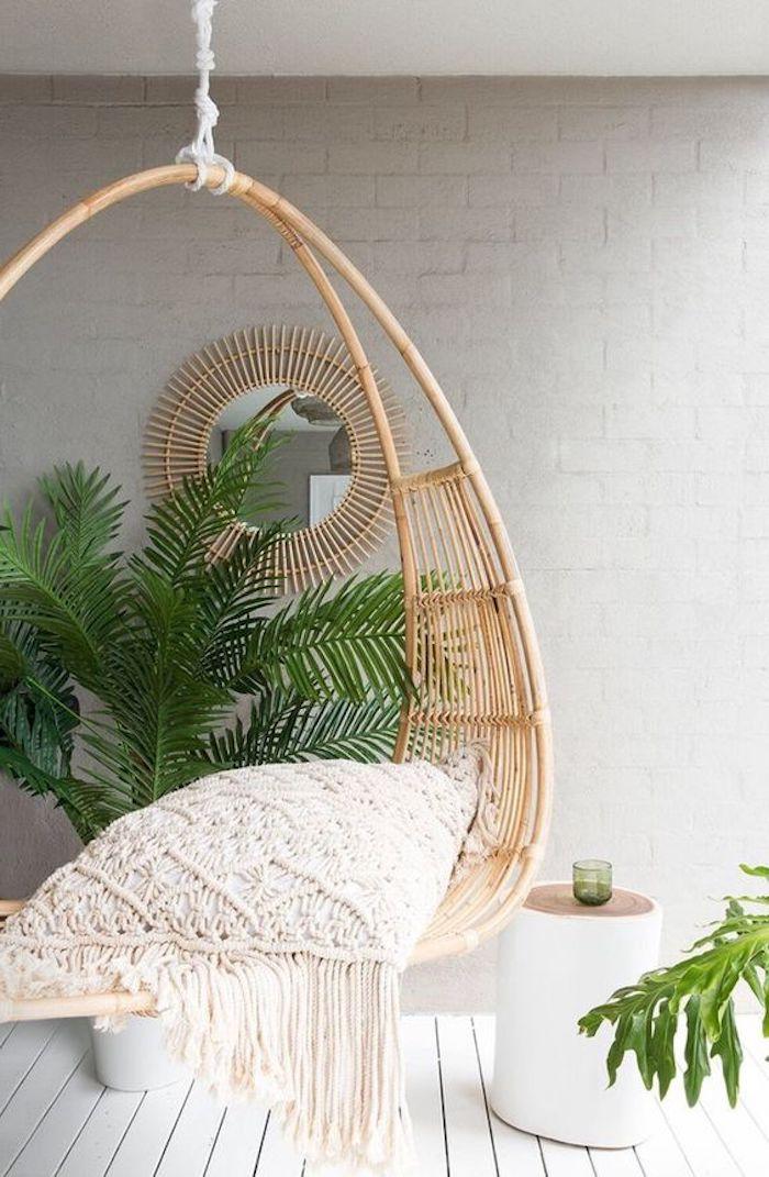 une chaise pendante devant une palme en chache pot repeindre chaise en rotin