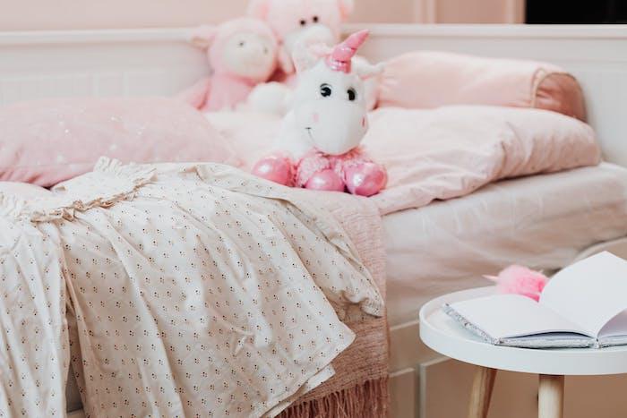 une chambre de petite fille avec une robe et un licorne en peouche sur le lit