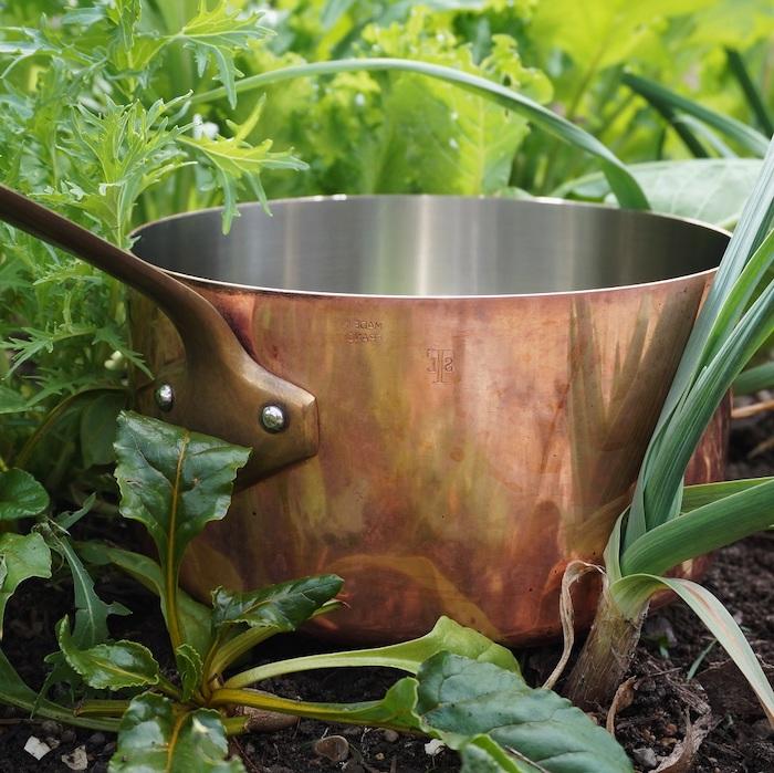 une cocotte en cuivre posé dans le jardin astuce jadinage potager