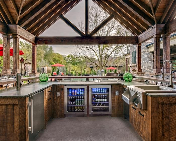 une cuisine extérieure dans une véranda aménagé en u avec frigo un evier et une vue vers la piscine