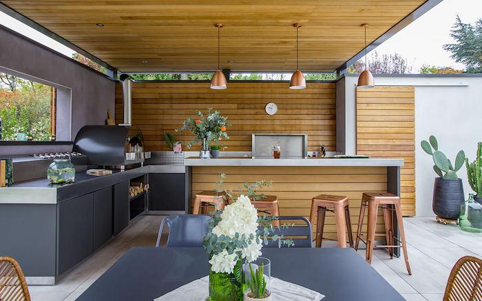 une cusine veranda moderne avec des surfaces en bois et des meubleus cuivrés des grands cactus au fond