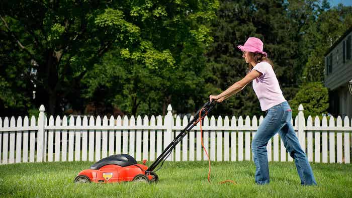 une femme avec chapeau rose tond la pelouse dans la cour derrière la palissade