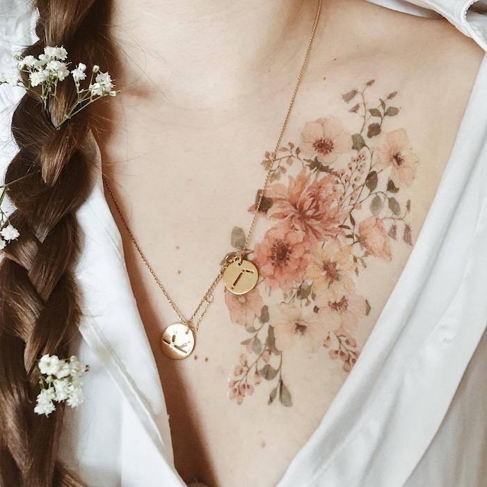 une femme avec des cheveux tressées et un dessin tatouage fleur sur la poitrine