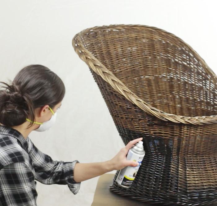une femme avec masque peint une chaise en rotin avec de la peinture en aérosole