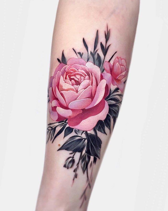 une femme avec tatouage rose avant bras des feuilles noirs