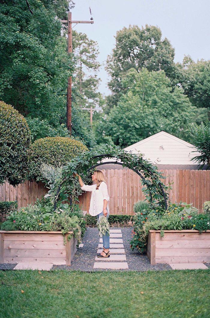 une femme dans le jardin sous un arc en verdure cuillit des feuilles idee bordure jardin recup