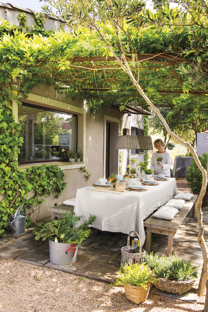 une femme derriere la table a manger sous une toiture naturelle de vignes