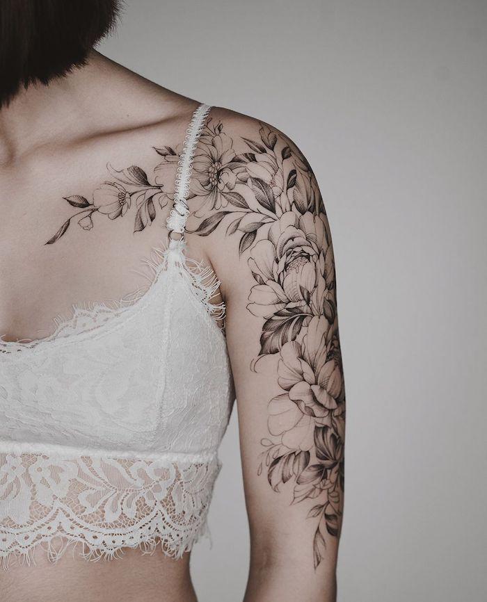 une femme en bralette blanche et cheveux courts noir une tatouage fleur epaule en noir et blanc