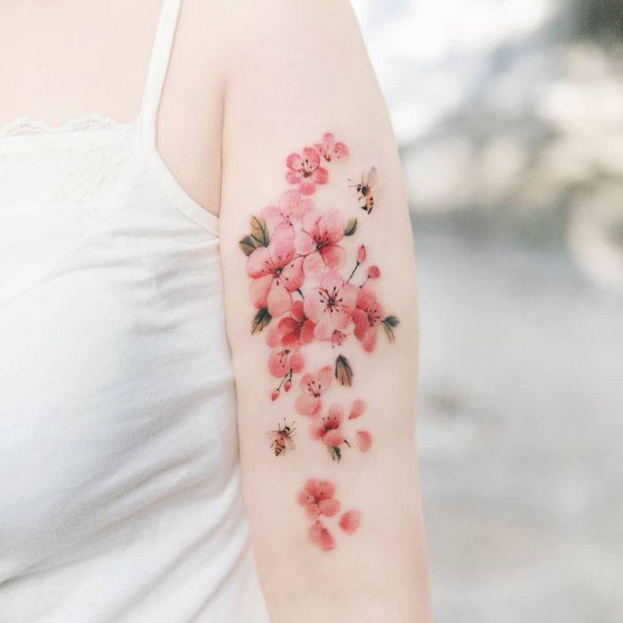 une femme en top banc avec un fmeur de cerisier tatouage fin au bras