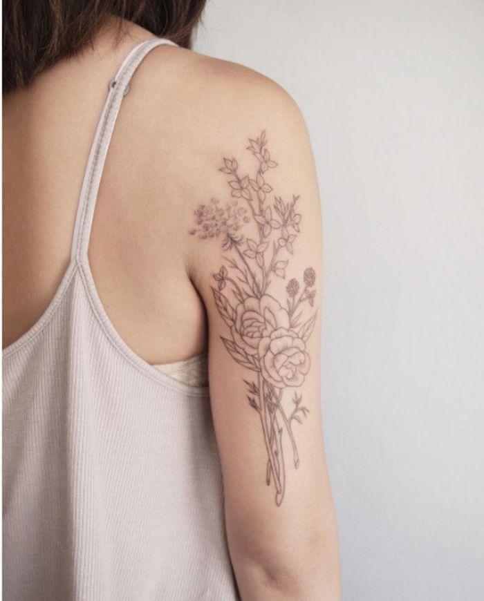 une femme en top beige et tatouage plante sur le bras