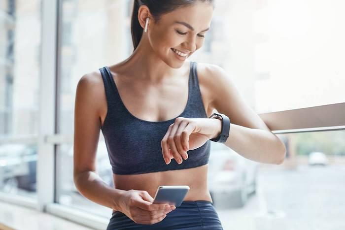 une femme en vetements de sport regarde le montre sur sa poignée portable dans le main