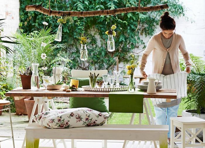 une femme qui met la table dans une véranda décoré det bouteilles avec des fleurs pendantes et multitude de verdure