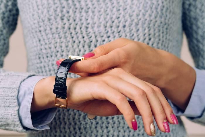 une femme qui se met un montre avec elements dorés sur la poignée