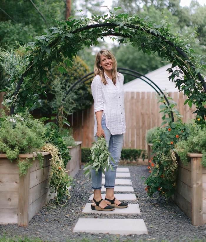 une femme qui tient des branches vertes entourée des plantes dans grandes coffres en bois