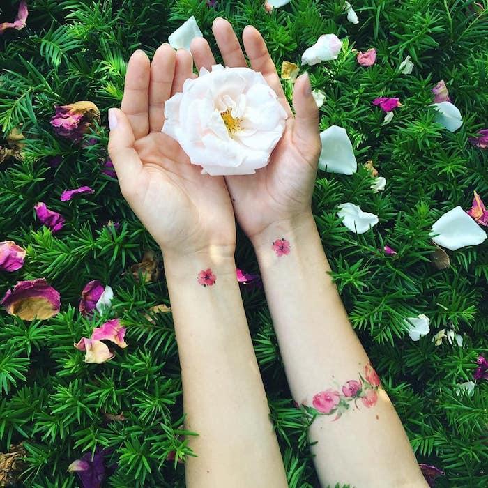 une femme qui tient rose blanche avec un tatouage nature sur les pognets