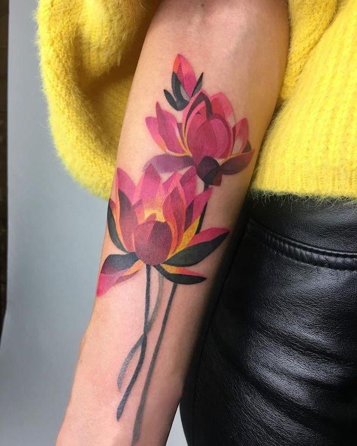 une femme vetue en pantalon en cuir et pull jaune avec tatouage orchidée sur l avant bras