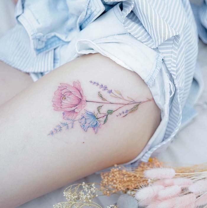 une femme vetue en pyjama avec un tatouage des fleurs de champ sur la cuisse