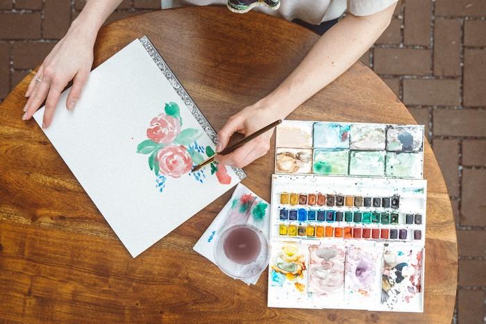 une fille qui dessine des fleurs a l aquqrelle sur un feuille de papier table en bois ronde