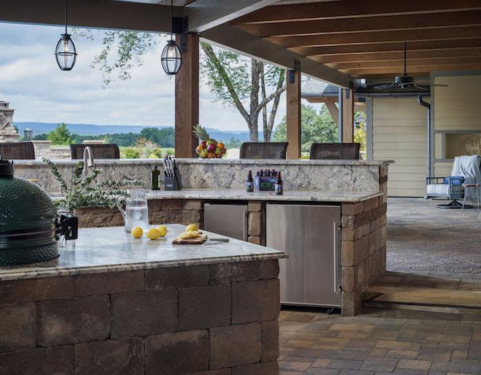 une grande veranda extérieures équipée de cuisine et d une grille avec vue vers le champ