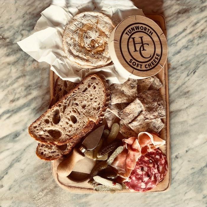 une idée d accompagnement de camembert avec des cornichons et charcuterie sur un plateau en bois