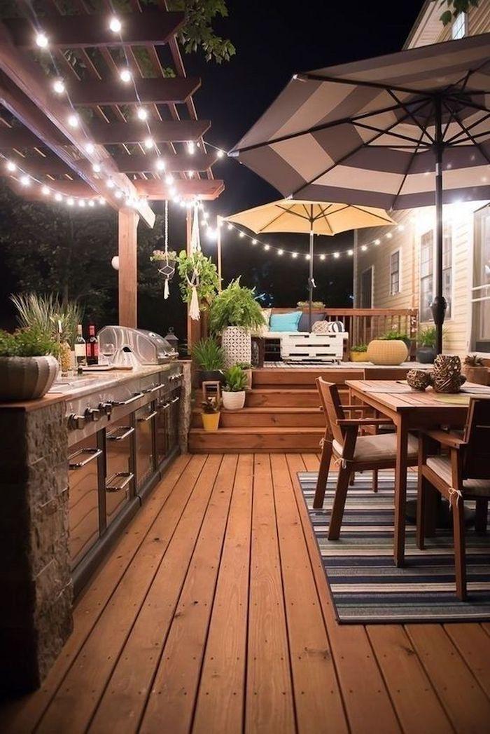 une idée d aménagement veranda 20m2 avec des guirlandes de lumièeres et deux parasols un tapis a rayures sur le sol