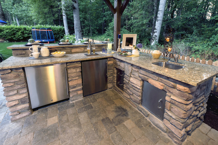 une idée d aménagement veranda avec une cuisine en angle construit des pierres dans le jardin