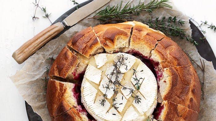 une idée de camembert en croute avec de marmelade et de romarin servi sur papier avec un couteau