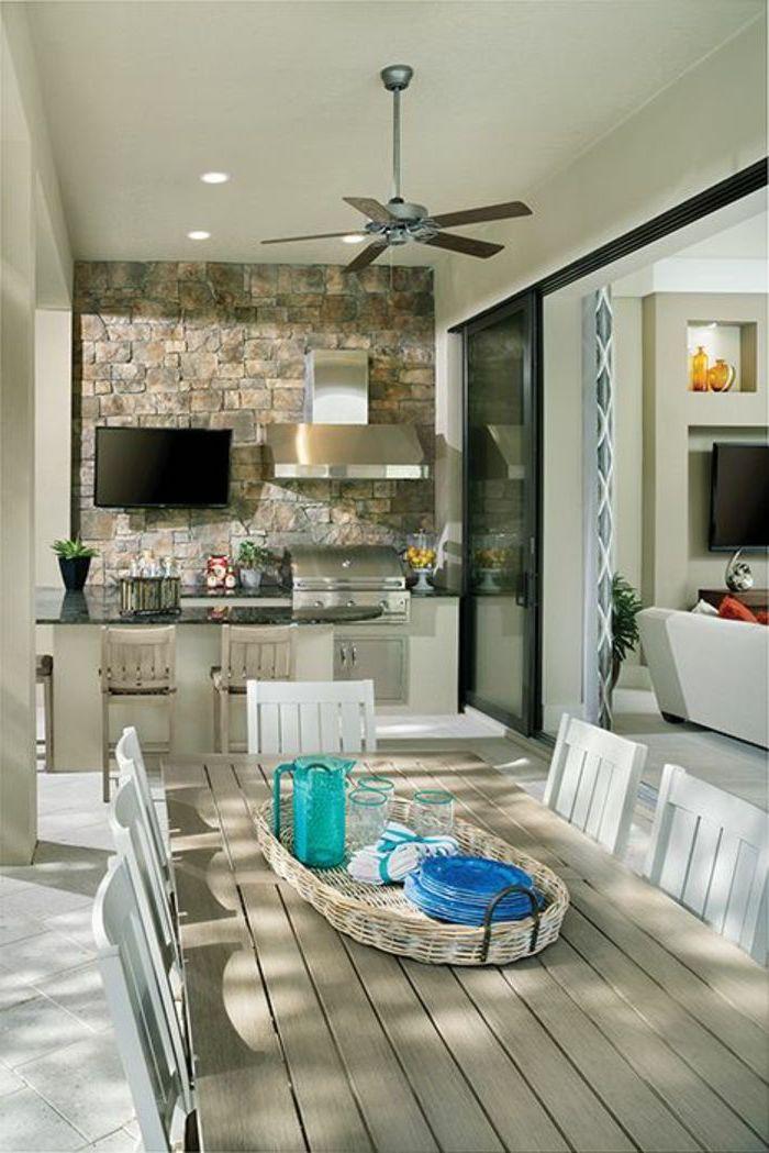 une idée de cuisine dans veranda aménagé avec une grille et aspirateur une salle a manger avec des chaises au milieu de l espace